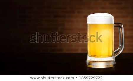 Glass of lager beer with foam and bubbles on stone board on black background. Stock photo © DenisMArt