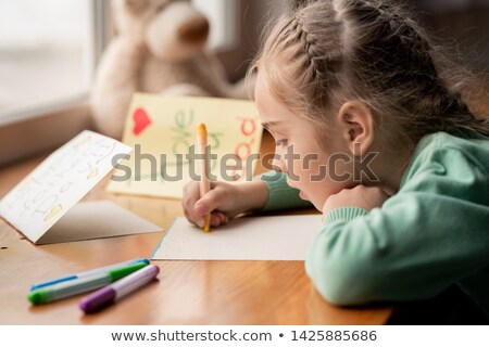 Concentrated girl making postcard for daddy Stock photo © pressmaster