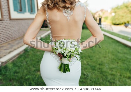 the bride socks her back to the frame and holds a bouquet of colorful flowers stock photo © ruslanshramko