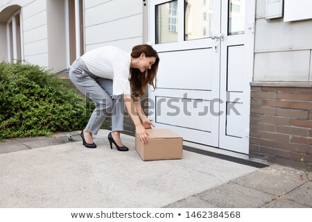 Young Woman Peeking Up The Delivered Parcel Stock photo © AndreyPopov