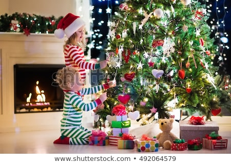 happy girl in santa hat decorating christmas tree Stock photo © dolgachov