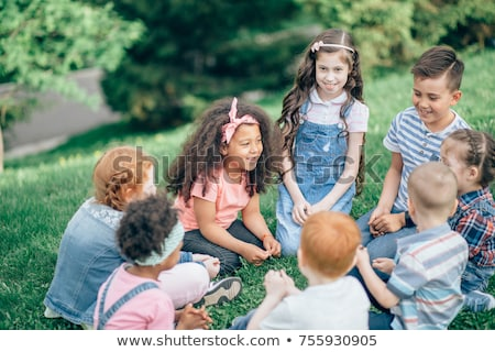 Group of young friendly intercultural people sitting on playground after game Stock photo © pressmaster