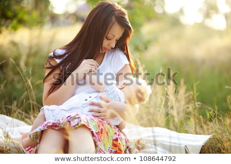 young mother feeding milk the infant baby outdoors Stock photo © Lopolo