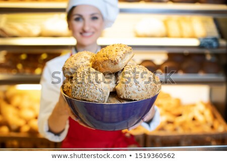 Fresh bread presented by an attractive young sales woman in bakery Stock photo © Kzenon