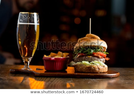 Beef burger in homemade pizza dough bun with BBQ sauce, melted c Stock photo © boggy
