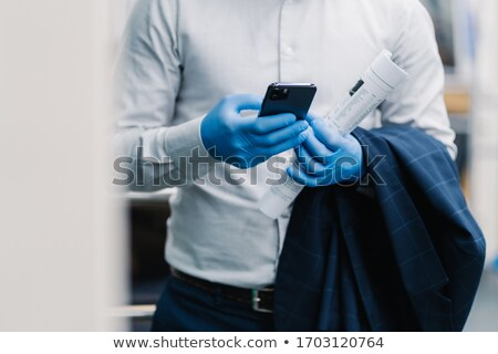 Unrecognizable businessman in elegant clothes types message on modern smartphone, wears protective d Stock photo © vkstudio
