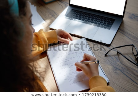 Young woman using a laptop computer and  a pen and paper Stock photo © photography33