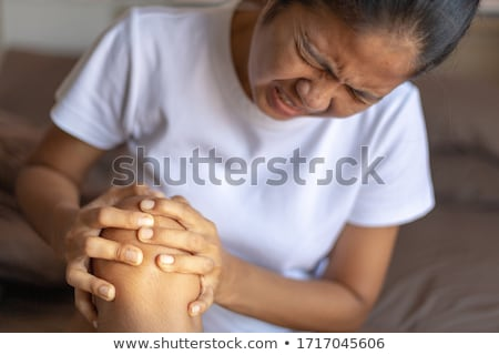 Woman holding sore leg, white background Stock photo © Nobilior