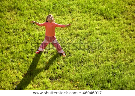 Little girl is standing having stretched hands on water drain hatch in grass field. long shadow on g stock photo © Paha_L
