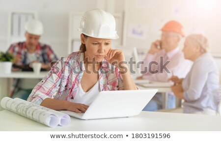group of people working with laptop smartphone and blueprint stock photo © deandrobot