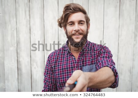 Smiling Bearded Man Against Wooden Wall Stock photo © ozgur