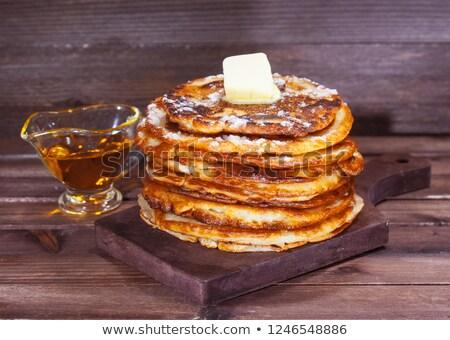 Pancakes with fresh berries and maple syrup on dark background, closeup Stock photo © yelenayemchuk