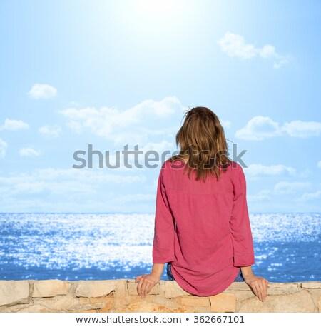 Giovane ragazza seduta muro di pietra muro divertimento magazine Foto d'archivio © IS2