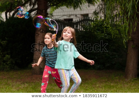 Girl playing with bubbles in backyard Stock photo © IS2