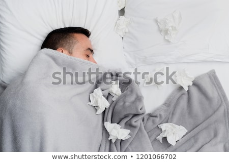 ill man in bed surrounded by used tissues Stock photo © nito