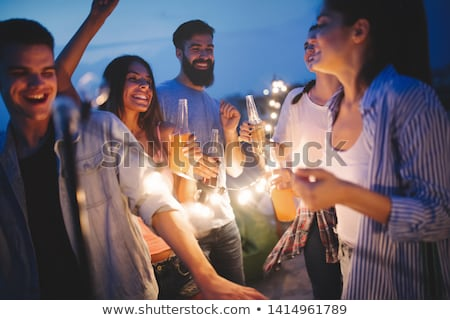 friends with party cups on rooftop at night Stock photo © dolgachov