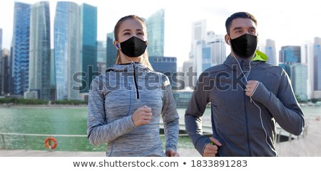 couple with earphones running over singapore  Stock photo © dolgachov