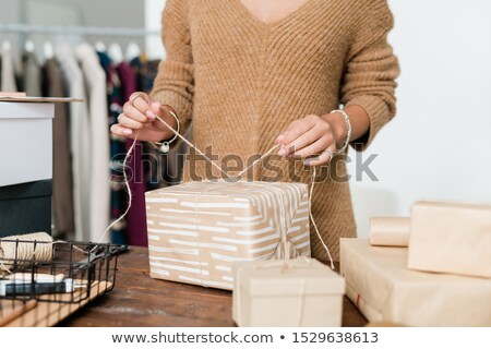 Young casual woman in knitted pullover binding thread on top of wrapped giftbox Stock photo © pressmaster
