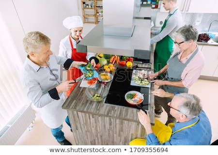 Group learning cooking in training kitchen with nutritionist Stock photo © Kzenon