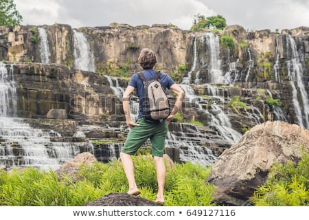 Man hiker, tourist on the background of Amazing Pongour Waterfall is famous and most beautiful of fa Stock photo © galitskaya