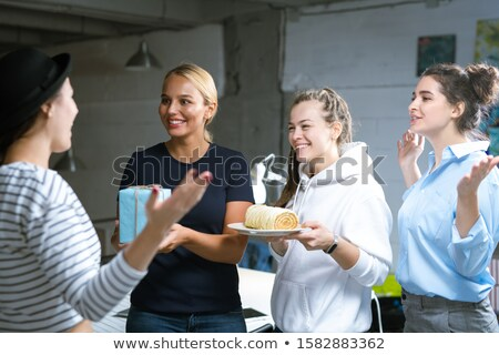 Three cheerful young women congratulating their colleague on her birthday Stock photo © pressmaster