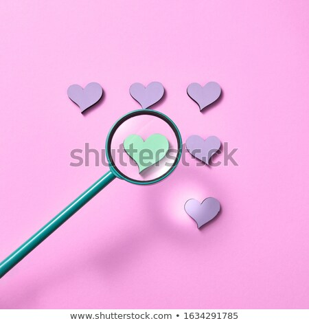 Magnifying glass above pink background with shadows. Stock photo © artjazz