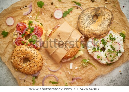 Bagels with ham, cream cheese, hummus, radish wrapped in brown baking paper ready for take away Stock photo © dash