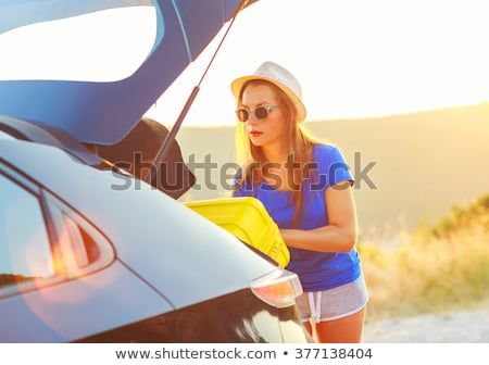 Woman loading luggage into the back of car parked alongside the  Stock photo © vlad_star