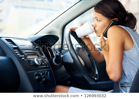 Stock photo: Businesswoman multitasking while driving, drinking coffee and ta