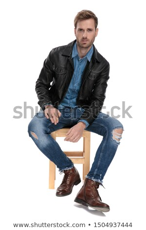 young man in leather jacket resting on a chair stock photo © feedough
