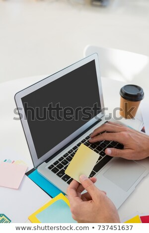 cropped hands of graphic designer holding adhesive note while using laptop stock photo © wavebreak_media