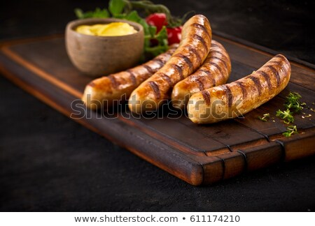 grilled sausage on dark rustic wooden background stock photo © yelenayemchuk