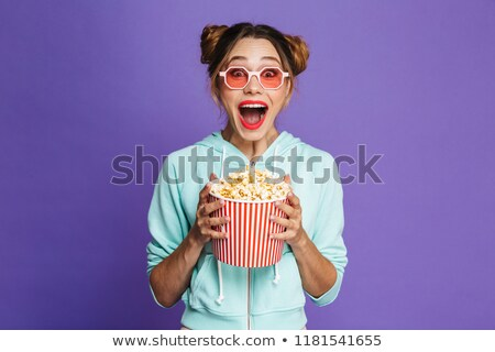 Photo of excited woman 20s in sunglasses smiling and holding pre Stock photo © deandrobot