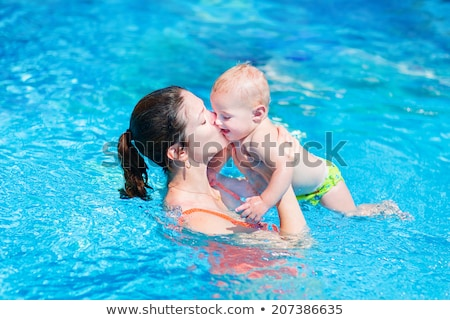 Young mother teach her little son, how to swim in a swimming pool Stock photo © galitskaya