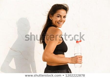 Full length image of feminine woman 20s holding bottle with wate Stock photo © deandrobot