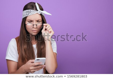 photo of shocked woman 20s holding and using mobile phone isola stock photo © deandrobot