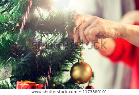 close up of senior woman decorating christmas tree stock photo © dolgachov