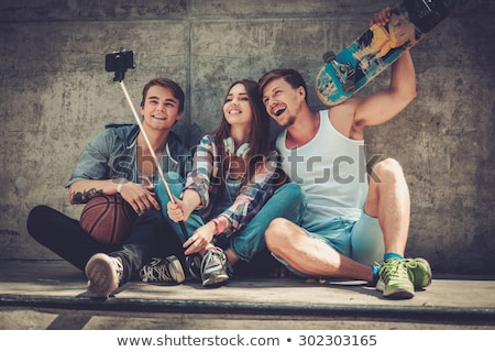 friends taking picture by on selfie stick in city Stock photo © dolgachov