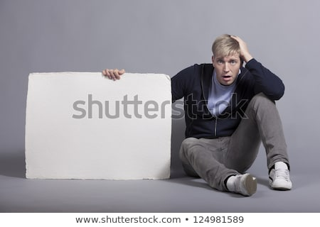 Disoriented man holding white empty panel. Stock photo © lichtmeister
