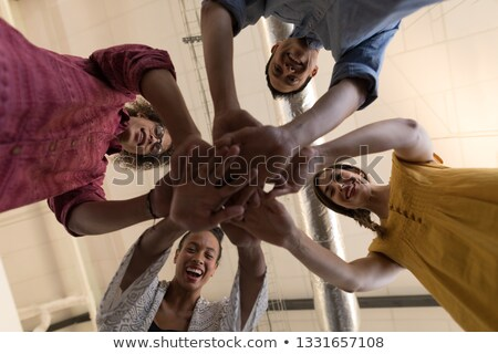 Low angle view of diverse casually dressed business colleagues forming hand stack in office Stock photo © wavebreak_media