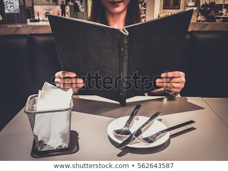 Beautiful woman ordering from menu in restaurant and deciding what to eat Stock photo © galitskaya