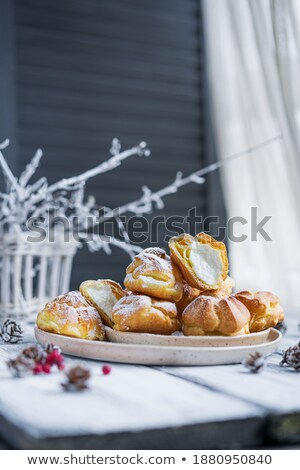 Profiteroles with powdered sugar on wooden background. Rustic style. Stock photo © Illia
