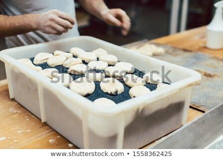 Baker putting poppy seed on raw bread rolls Stock photo © Kzenon