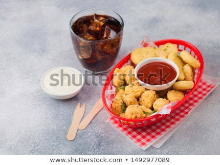 Buttered chicken nuggets and popcorn bites in red fast food basket with ketchup and glass of cola on Stock photo © DenisMArt