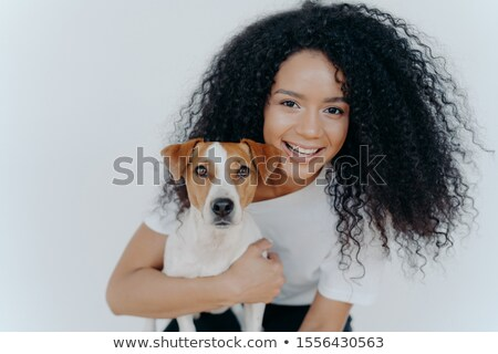 Close up shot of pleased smiling woman with bushy crisp hair, keeps eyes shut, smiles gently, wears  Stock photo © vkstudio