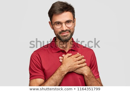 Portrait of handsome male employee has stubble, holds hands together, looks thoughtfully at camera,  Stock photo © vkstudio