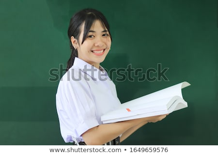 portrait of a young woman in front of a blackboard holding a piece of chalk in a classroom stock photo © wavebreak_media