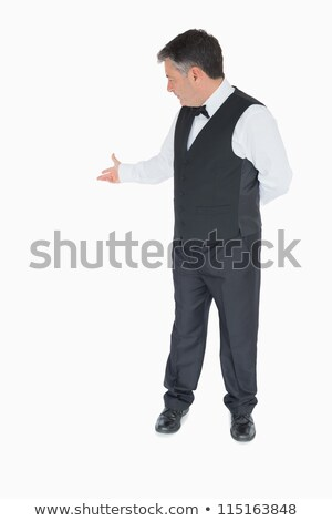 Stock photo: Waiter showing something behing him on white background