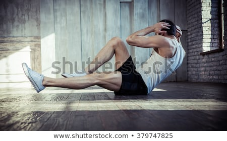 Muscular young man  pressing-ups Stock photo © konradbak