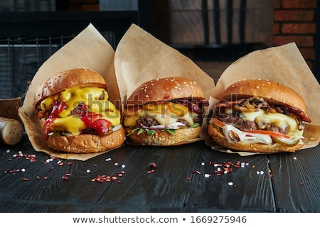 Three appetizing burgers on wooden table Stock photo © jeliva